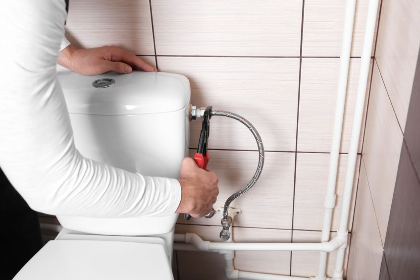 Plumber fixing toilet cistern