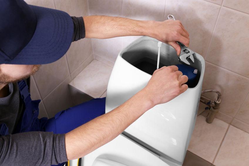 Plumber repairing toilet cistern